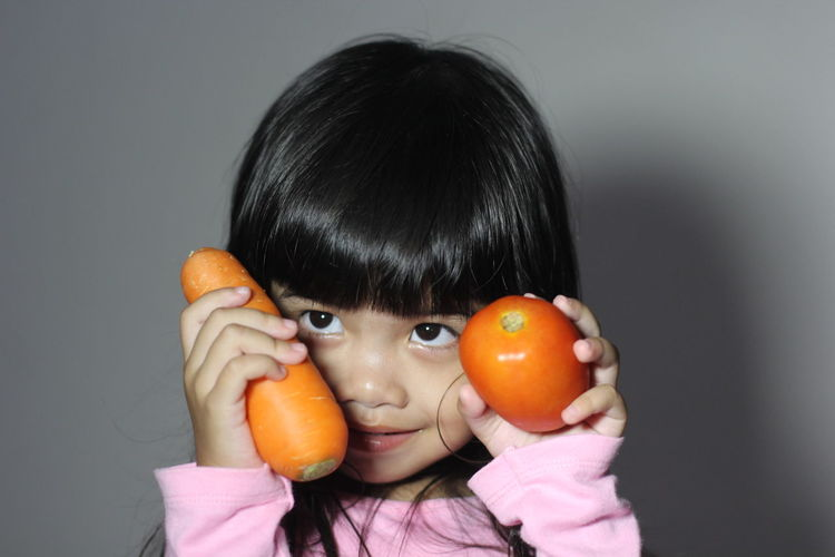 Close-up portrait of a girl holding fruit over white background