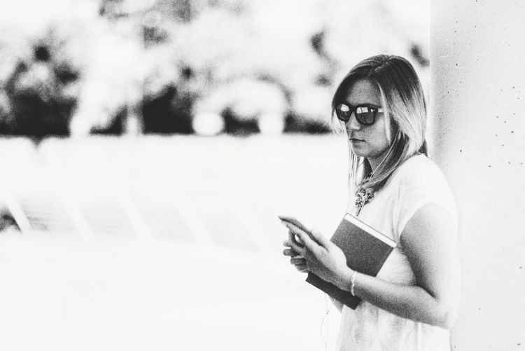 Woman with book using phone while leaning on column outdoors