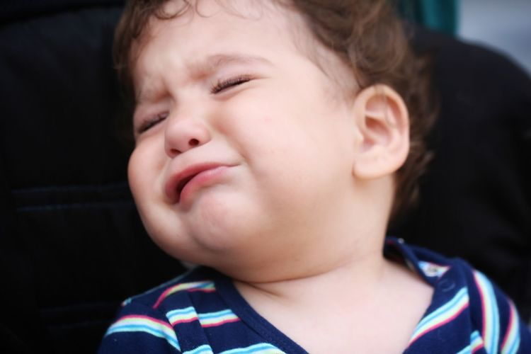 Close-up of cute baby boy crying while sitting on chair
