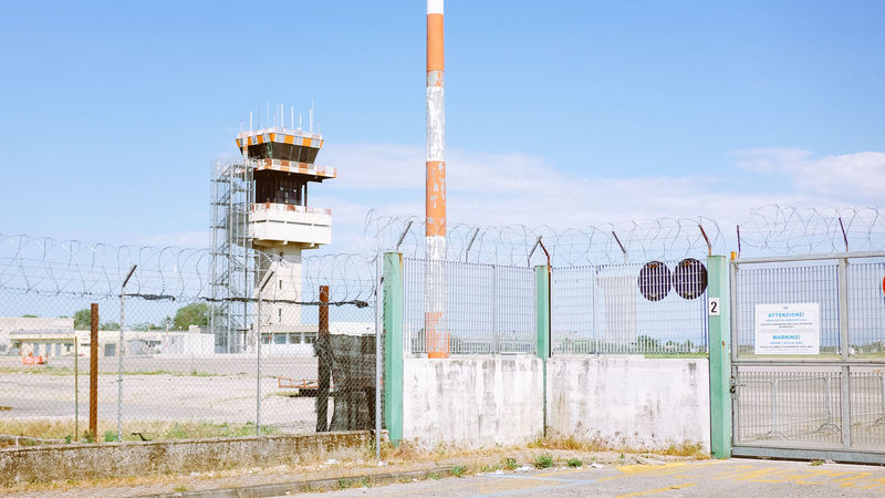 Fence in front of an airport control tower Airplane Airport Boundary Built Structure Centre Control Panel Day Fence Fences Military No People Outdoors Restricted Sky Technology Tower Town The Secret Spaces
