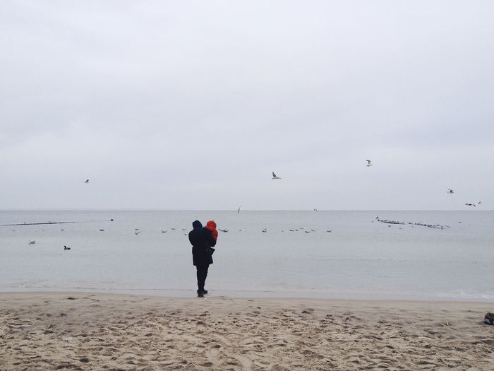 Mother with baby standing at the beach with sea gulls, Rügen Beach Beauty In Nature Bird Cold Family Horizon Over Water Horizontal Minimalism Minimalist Outdoors Real People Rear View Scenics Sea Sea And Sky Seagull Seascape Water Neighborhood Map