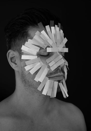 Close-up of shirtless man with papers on face against black background