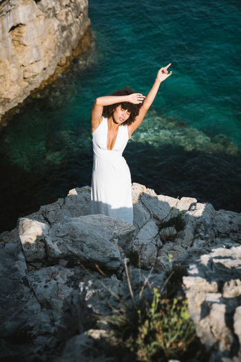 One Person Rock - Object Solid Rock Leisure Activity Young Adult Real People Water Lifestyles Women Nature Full Length Young Women Sea Dress White Color Beauty In Nature Fashion Outdoors Beautiful Woman Hairstyle Human Arm Arms Raised