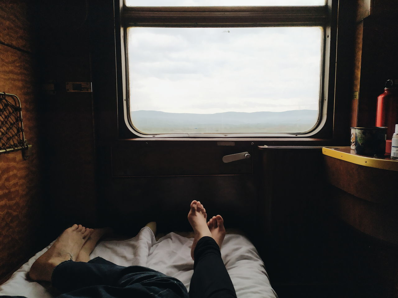 Low section of people lying in vehicle by window