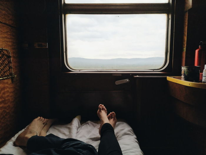 Low section of man lying on train window