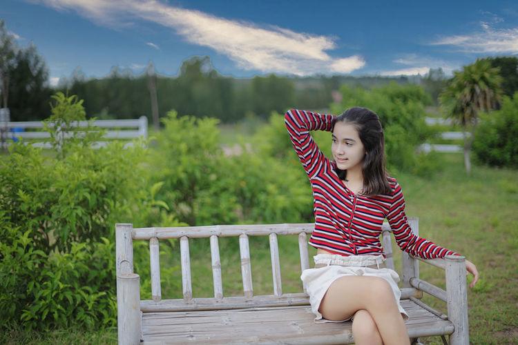 Woman sitting on bench in field
