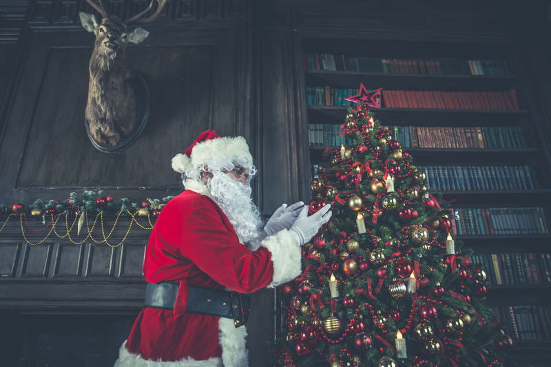 Side view of man wearing santa claus costume standing by christmas tree at home