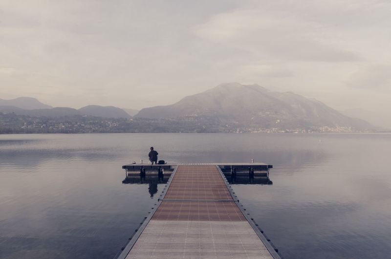 Man on pier on lake against sky