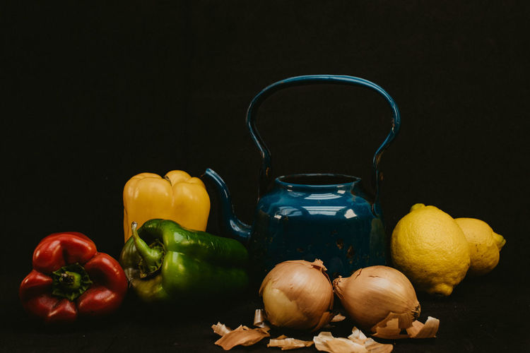 Close-up of fruits and vegetables on table against black background