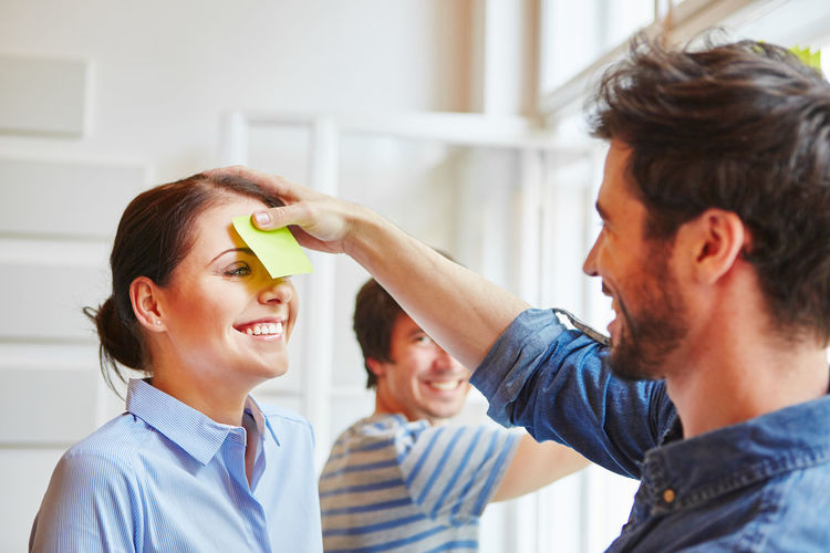 Smiling Businessman Sticking Adhesive Note On Businesswoman Face