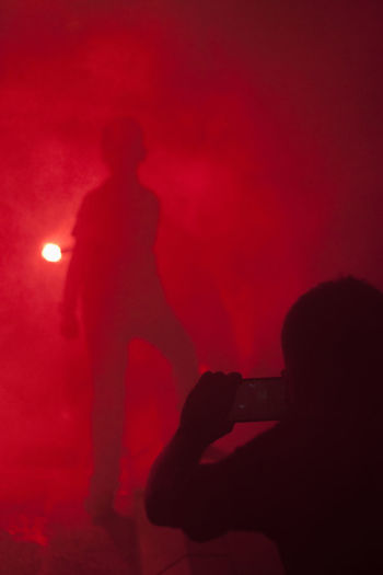 Rear view of silhouette man with arms raised