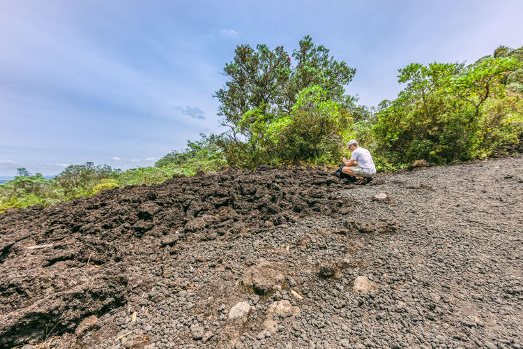 Side view of man crouching on hill against sky