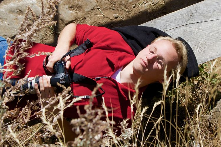 High angle view of photographer lying down on bench during sunny day