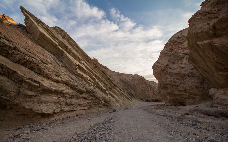 Dirt road passing through rock formation against sky
