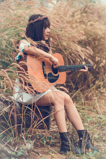 Musical Instrument Guitar String Instrument Music Playing Land Sitting One Person Real People Leisure Activity Plant Field Holding Full Length Grass Plucking An Instrument Arts Culture And Entertainment Musical Equipment Nature Young Adult Acoustic Guitar Hairstyle Outdoors Beautiful Woman