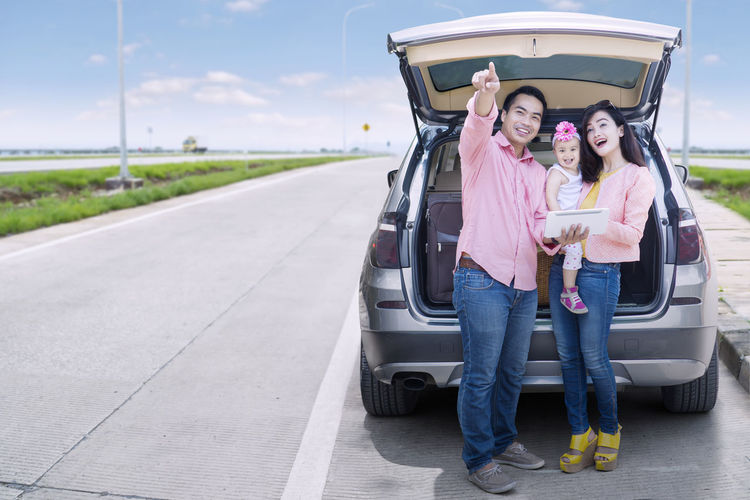 Father pointing while standing with family against car trunk on road