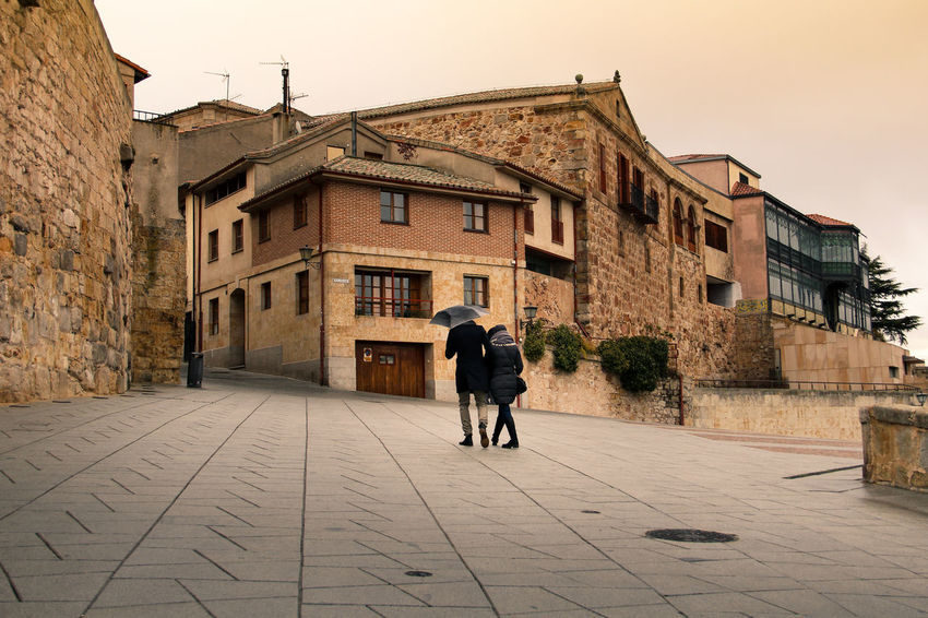 Couple walking in the romantic streets of a Spanish old town. Architecture Cold Weather Couple Moody Sky Old Town Raining Romantic SPAIN Salamanca Spanish Architecture Spanish Town Building Exterior Built Structure Couple Walking Couple Walking In Old Town Historical City Historical Place Moody Weather Old Houses Rear View Salamanca Old Town Soft Colors  Spanish Culture Umbrella Warm Colors