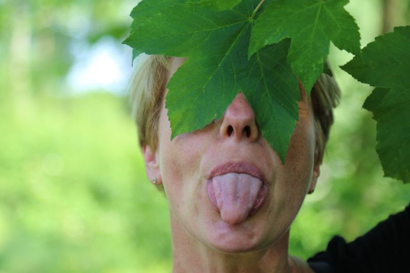 Close-up of woman covering eyes with maple leaf while sticking out tongue