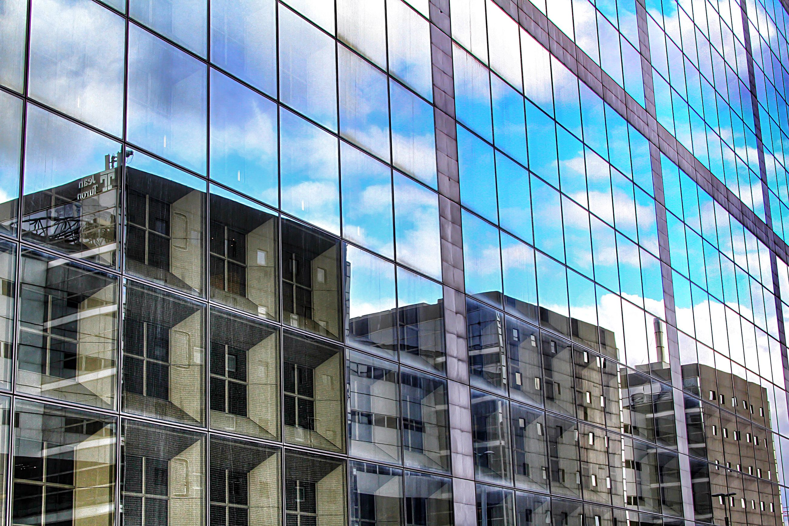 architecture, building exterior, built structure, modern, glass - material, office building, low angle view, city, reflection, window, building, skyscraper, blue, glass, sky, tall - high, day, tower, city life, outdoors