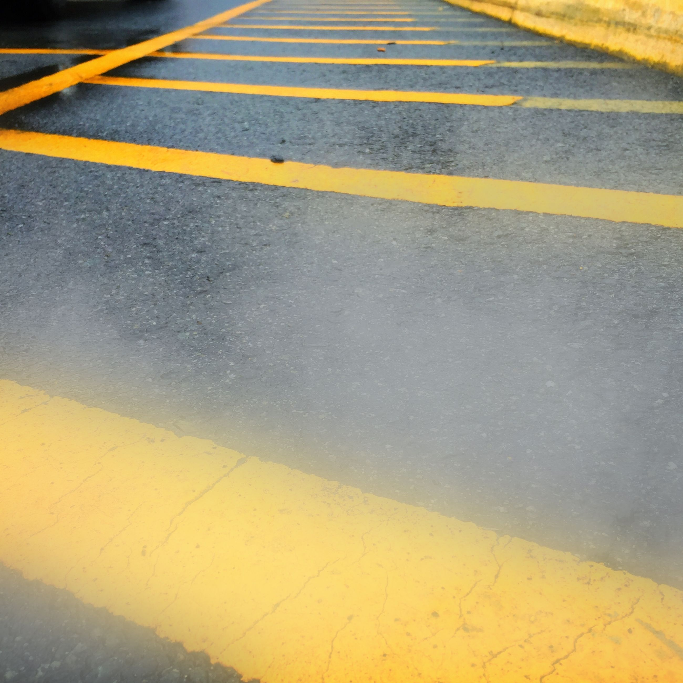transportation, road marking, asphalt, road, the way forward, street, high angle view, yellow, outdoors, vanishing point, diminishing perspective, mode of transport, no people, day, dividing line, sky, travel, surface level, nature, empty road