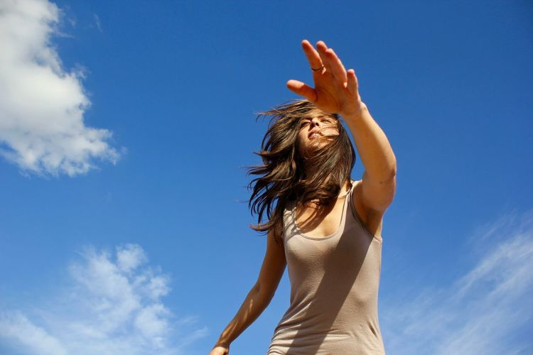 Low angle view of woman against blue sky