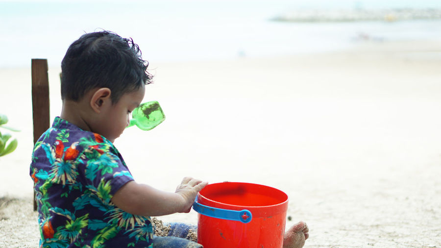 Baby boy playing with toy at beach