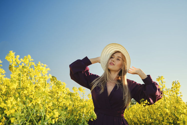 Young woman standing on yellow flowering plants against clear sky