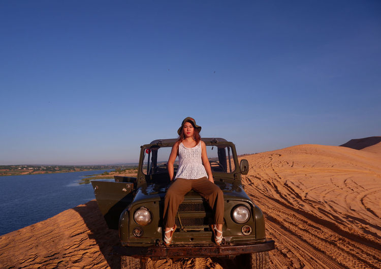 Portrait of woman sitting on off-road vehicle against clear blue sky