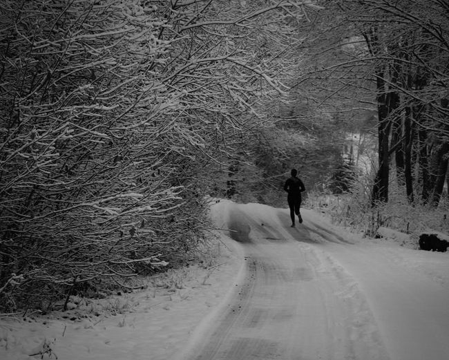 Rear View Of Man Running On Snow Covered Road