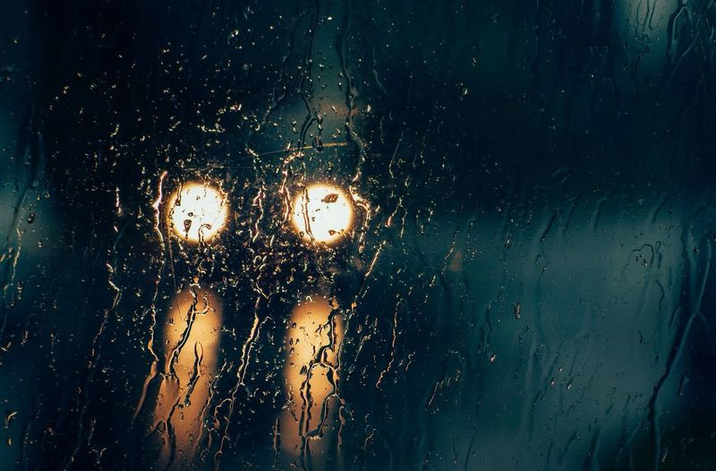 Waterdrops on glass with view of headlights at night