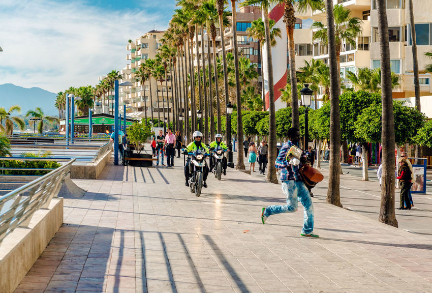 Marbella, Spain- January 8, 2014: Police on a motorbikes in pursuit of the street vendor. Marbella resort city. Malaga, Costa del Sol. Southern Spain Andalucía City Crime Detention Malaga Marbella Patrol  Promenade Pursuit  Quayside SPAIN Sidewalk Street Vendor Uniform Costa Del Sol Criminal Illegal Motorbike Outdoors People Police Safety Street Tourist Resort Waterfront