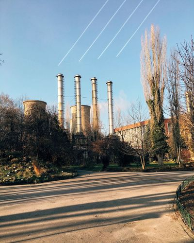 Low angle view of smoke stacks with vapor trails against sky
