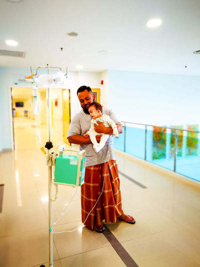 Father carrying cute daughter while standing in hospital corridor