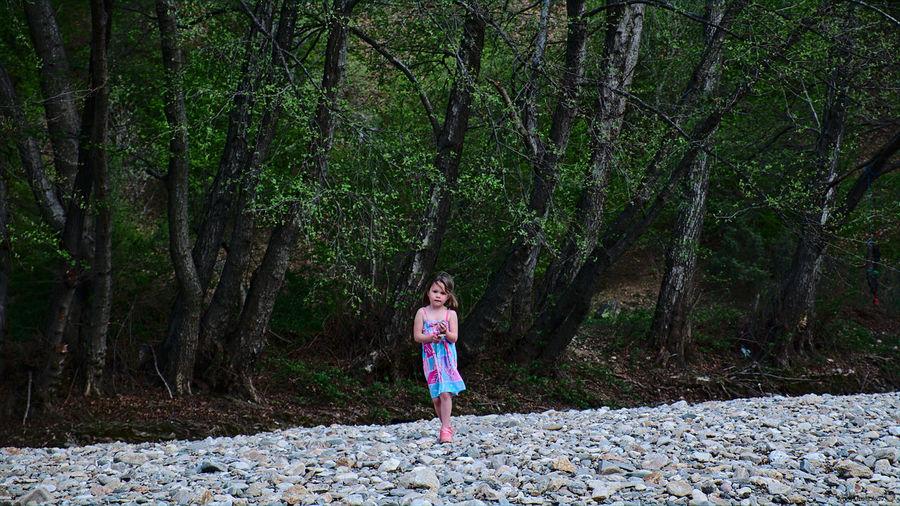 Girl walking on rocks against trees