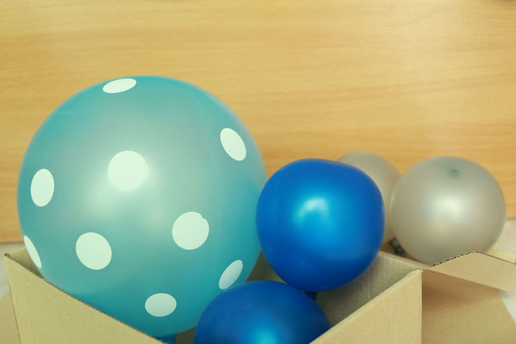 Indoors  Still Life Blue No People Table Close-up Multi Colored Ball High Angle View Sphere Celebration Shape Focus On Foreground Wood - Material White Color Easter Balloon Party Box Giving Gift