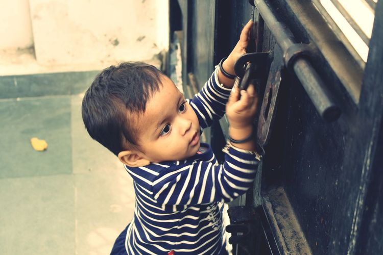 High Angle View Of Cute Baby Girl Opening Gate