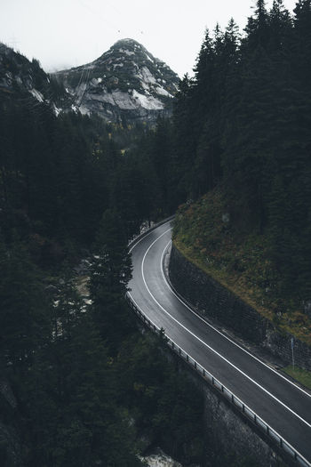 Empty road amidst trees and mountains in forest