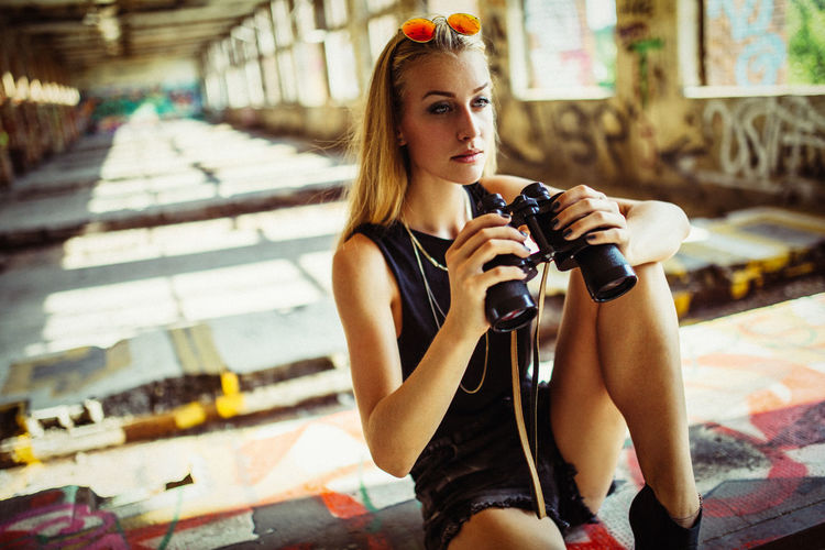YOUNG WOMAN HOLDING BINOCULARS