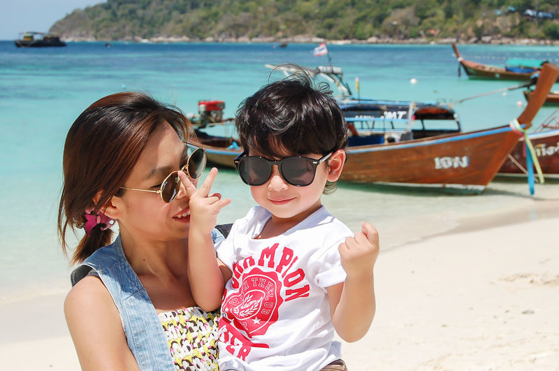 Mother and son in sunglasses against sea