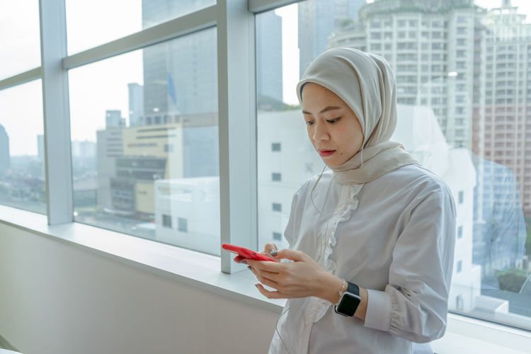 Young woman looking through mobile phone while standing on window