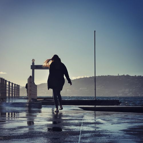 Rear view of woman walking on sea