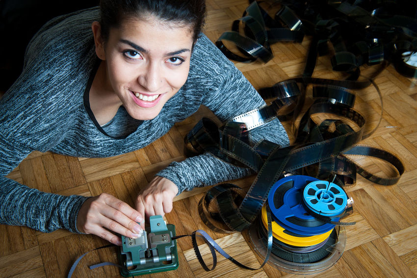 Young woman editing super 8 movie with reels and splicer Adult Adults Only Arts Culture And Entertainment Cinema Editing Film Filmstrips Indoors  MOVIE One Person One Woman Only One Young Woman Only Only Women People Post Production Smiling Splicer Super 8 Technology Women Working Young Adult