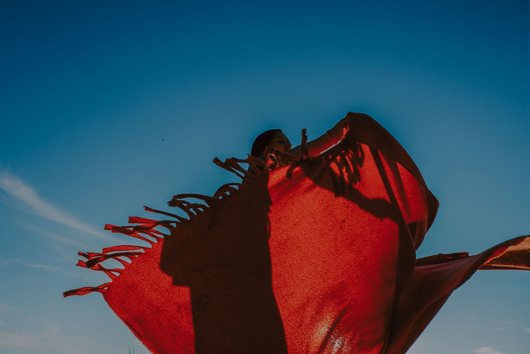 Low angle view of woman with red dress against blue sky