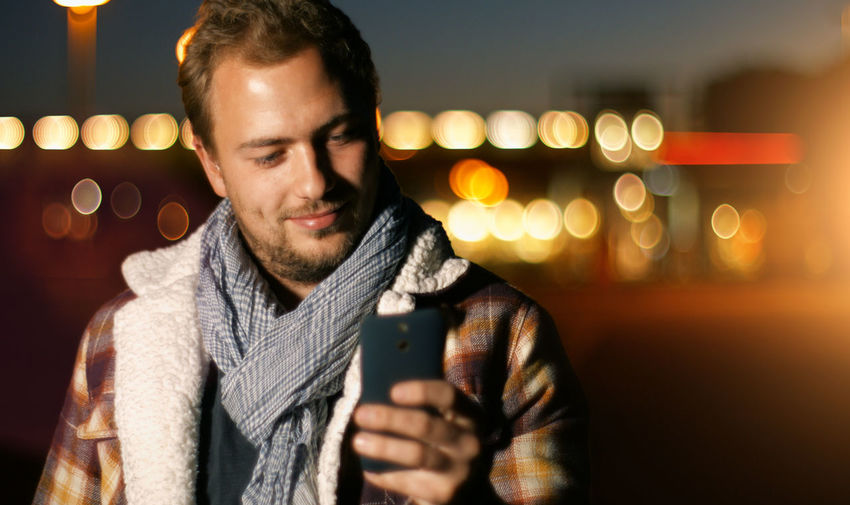 Smiling young man text messaging on mobile phone