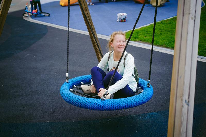 Smiling teenage girl sitting on swing at playground