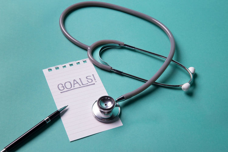 High angle view of stethoscope with paper and pen over blue background