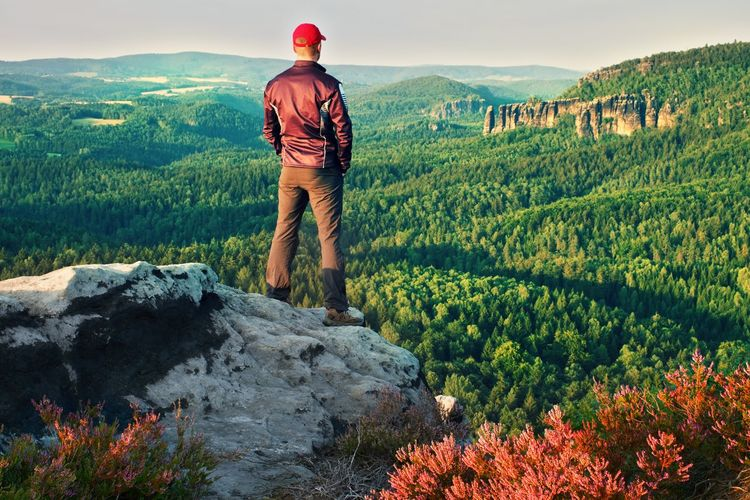 Tall man in black with red baseball cap on sharp cliff and watch to valley. colorful summer morning