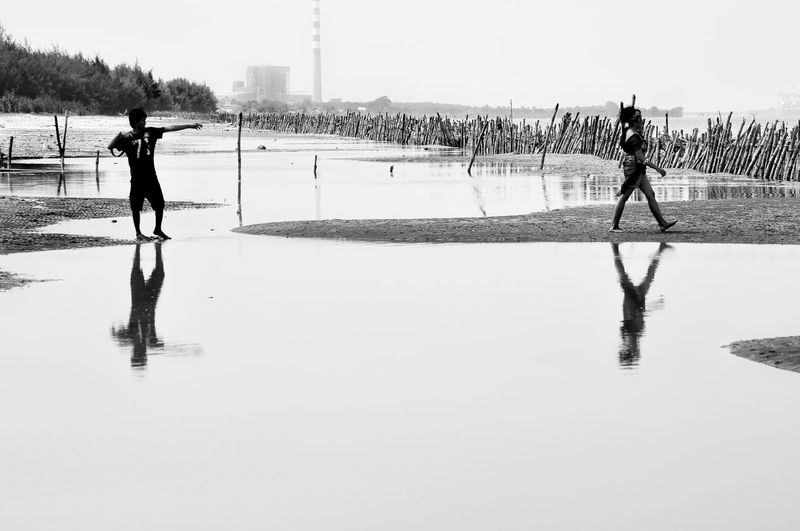 People walking on water against clear sky