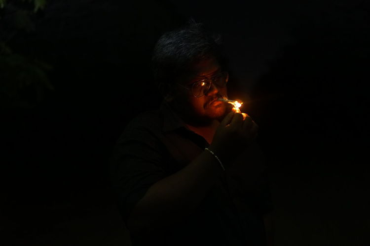 Man igniting cigarette in dark