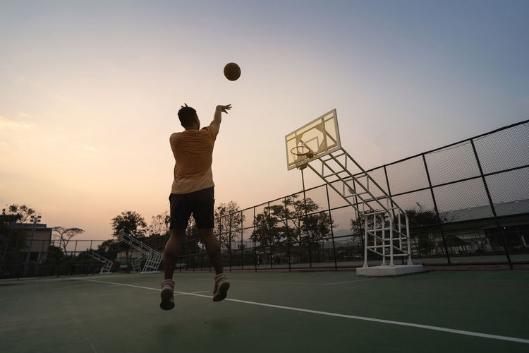 Man playing with ball against sky during sunset